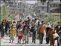 Palestinian refugees cross from the southern entrance of their besieged refugee camp.