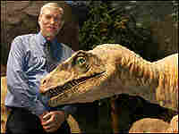 Ken Ham poses with a mechanical Utahraptor at The Creation Museum.