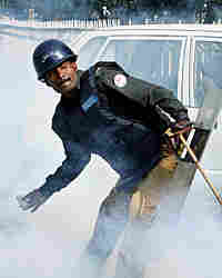 A Pakistani policeman throws a tear-gas shell toward lawyers during a protest in Lahore on Monday.