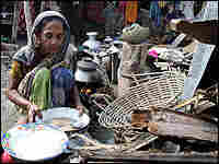 A woman prepares food in front of her destroyed house on the south coast of Bangladesh on Sunday.