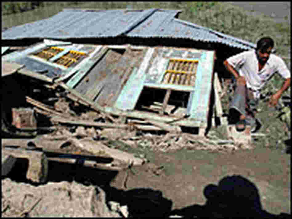 A man inspects his collapsed shop at a market in Gorjonbunia village in Bangladesh on Monday.