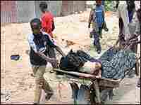 A Somali boy wheels his older brother's body