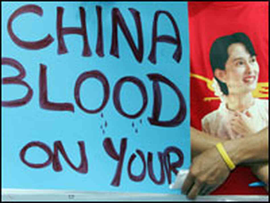 Myanmar activists display an anti-Chinese slogan and portrait of Aung San Suu Kyi.