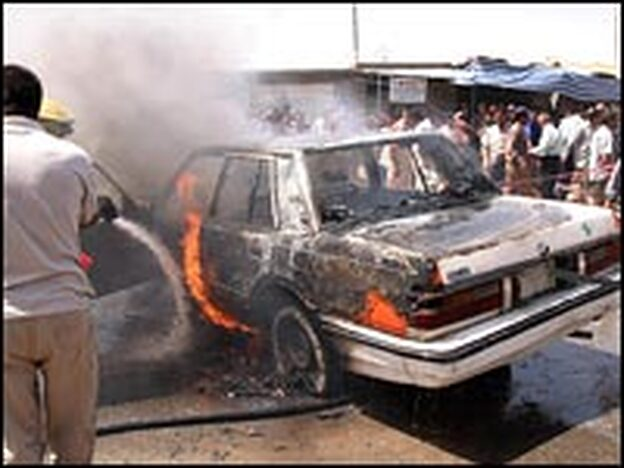 A burning vehicle is hosed down after a bomb attack in Kirkuk, Aug. 10, 2007.
