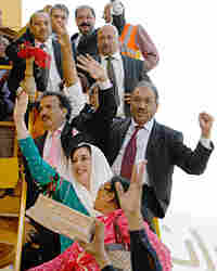 Former Pakistani Prime Minister Benazir Bhutto waves to followers on arrival in Karachi, Pakistan.