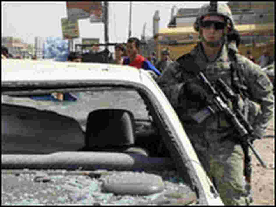 A U.S. soldier stands guard at the site of a car bomb attack in Baghdad on Monday.