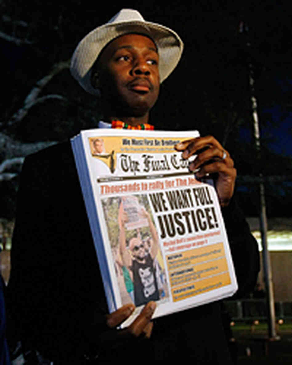 A man holds a newspaper before the start of a civil rights march in Jena, La., Thursday.