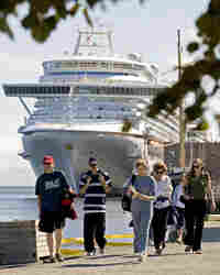 Tourists walk along the waterfront near the cruise ship Ocean Princess in Halifax, Nova Scotia.