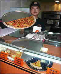 "A shopkeeper displays his wares at Shanghai's ""New York Pizza Parlor."""