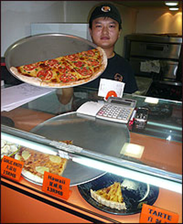"A shopkeeper displays his wares at Shanghai's ""New York Pizza Parlor."" The shop sells around 50 large pizzas every day; the increasing popularity of Western food means China's 1.3 billion residents are consuming more milk than before."