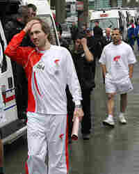 French former tennis player Arnaud Di Pasquale reacts as he carries an extinguished torch.