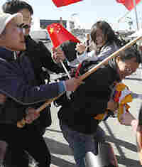 A man carrying a Tibetan flag is attacked by pro-China supporters.