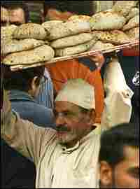 A vendor carries a rack of bread in Mahalla, Egypt.