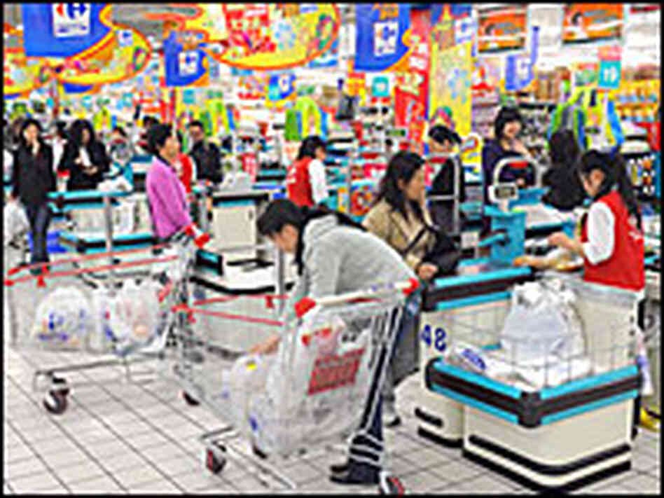Chinese shoppers stand at the check-out counters inside a supermarket in Shanghai