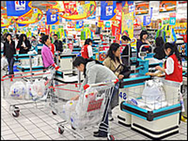 Chinese shoppers stand at the check-out counters inside a Carrefour supermarket in Shanghai on April 15, 2008. As China's population and national wealth grow, food costs — and inflation — have been rising.