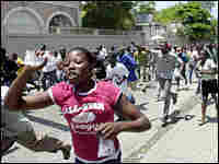 Haitians run through the streets in Port-au-Prince during protests against the rising cost of living