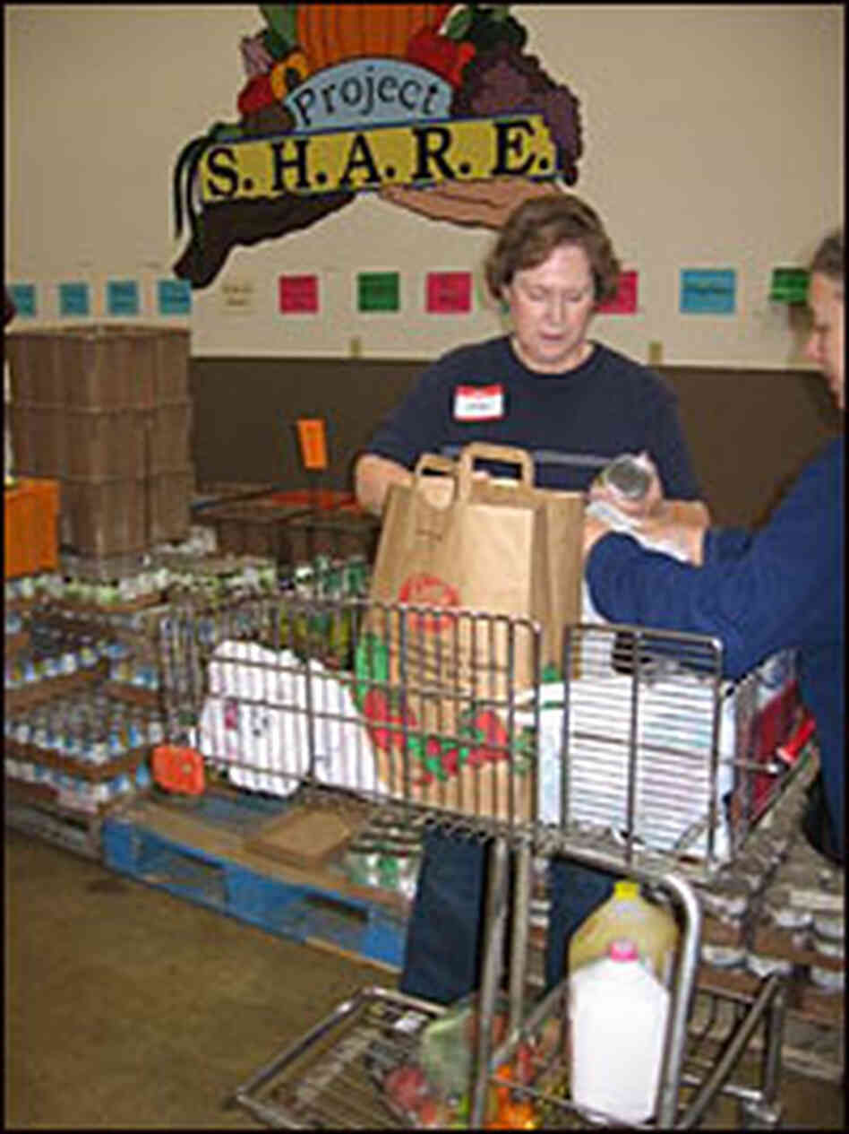 Volunteer hands out canned food at Project Share