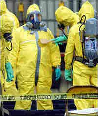 A hazmat response team member uses a brush to decontaminate a colleague in 2001.