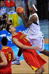 LeBron James jumps over Yao Ming during a men's preliminary round basketball match.