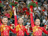 Members of China's women's gymnastics team hold up their gold medals and bouquets after their win