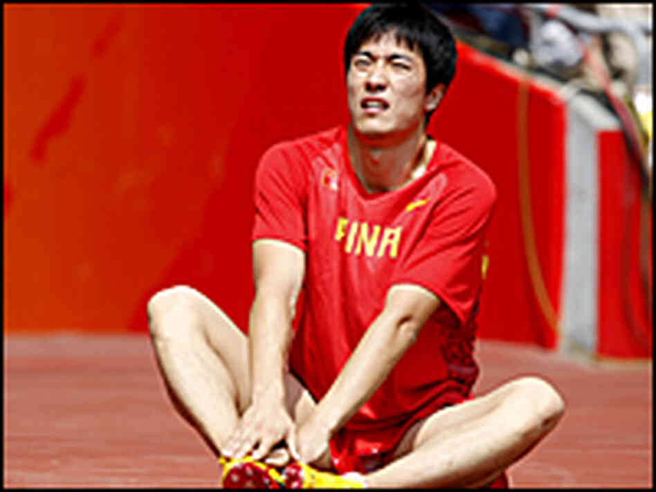 China's Liu Xiang sits on the ground after withdrawing from the 110-meter hurdles.