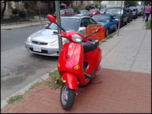 This Vespa is locked up on the sidewalk, away from road trouble.