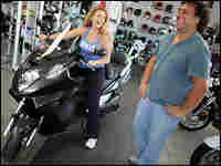Laura Rolo and Walter De Echave check out a 500cc Honda scooter in Miami, Fla.