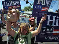 A protester holds up a Hillary sign and a rubber mask of Hillary Clinton.