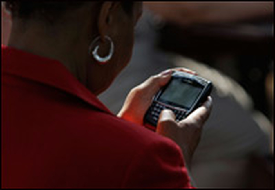 A woman works on her BlackBerry phone on Aug. 21, 2008, in Chester, Va., after she received instructions explaining how to get a text message from the Obama campaign announcing the identity of his running mate.