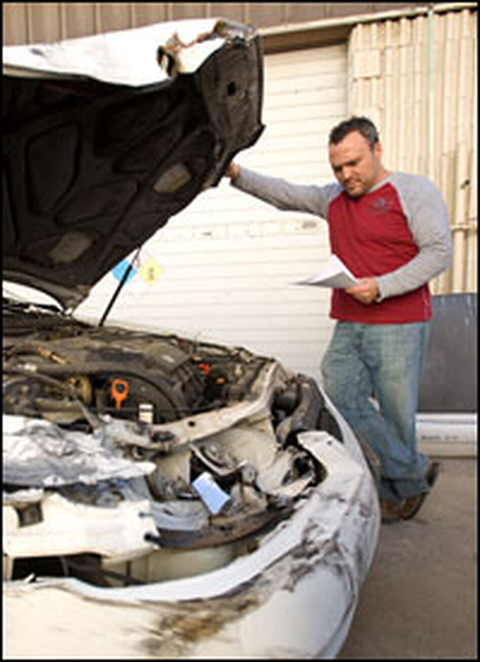 """Tavares inspects a damaged car. """"Any time there's a recession, it plays a huge factor in our business,"""" he says."""