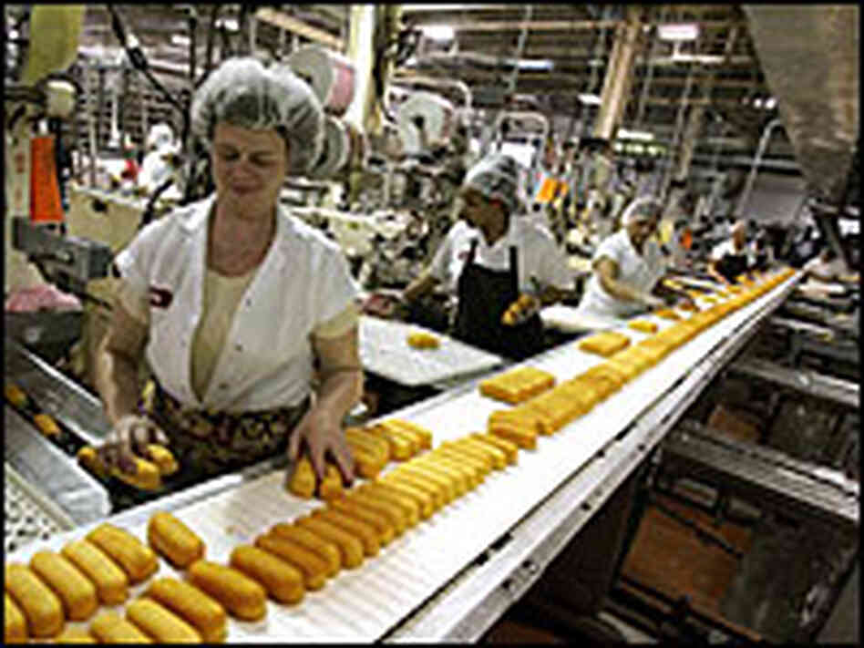 Factory workers preparing Hostess Twinkies for packaging.