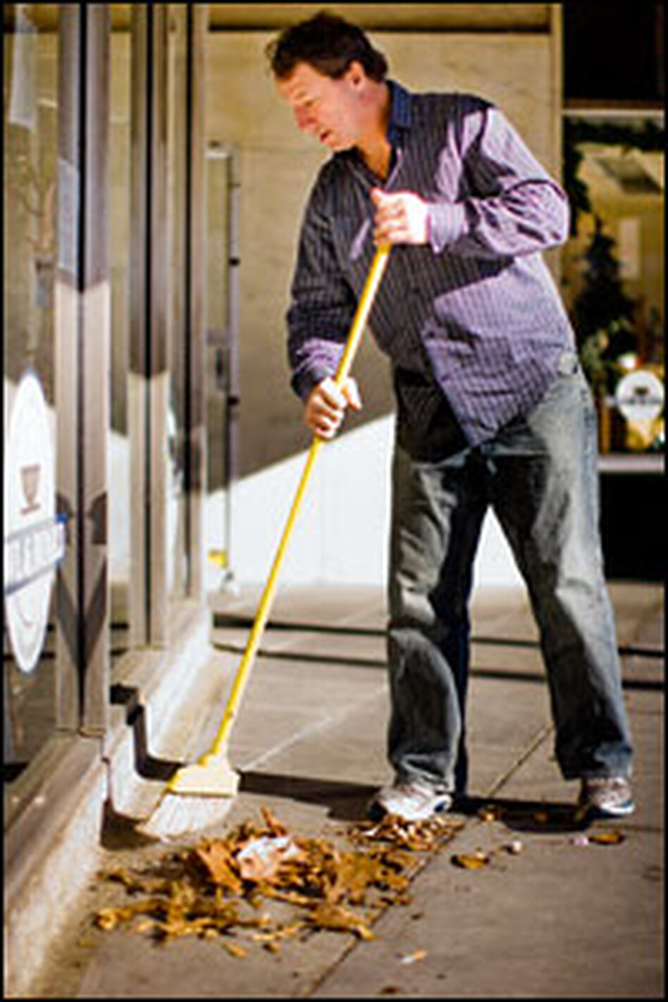 Mark Giarrusso sweeps in front of his Brookline, Mass., store.