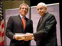 U.S. Holocaust Memorial Museum Chairman Fred Zeidman receives papers from Michael Mukasey.