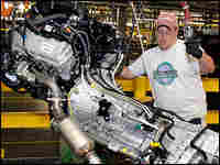 An assembly line worker installs an engine into a 2009 Ford F-150 truck.