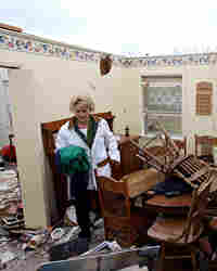 Becky Wilson searches through debris at her mother's house the morning after a tornado hit.