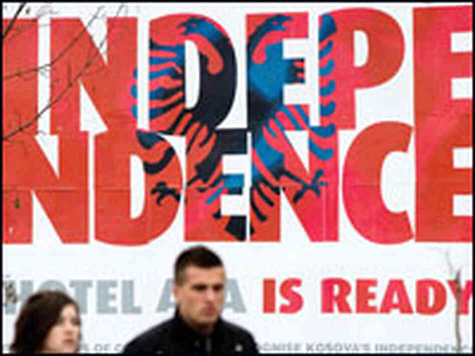"Ethnic Kosovo Albanians pass by a billboard reading ""Independence"" in Pristina, Kosovo."