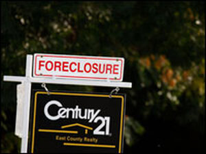 A sign reading foreclosed sits on top of a For Sale sign outside a home in Antioch, Calif.