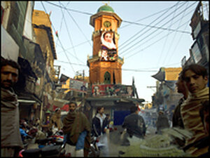A Benazir Bhutto PPP party campaign billboard is displayed above a busy bazaar in Peshawar.