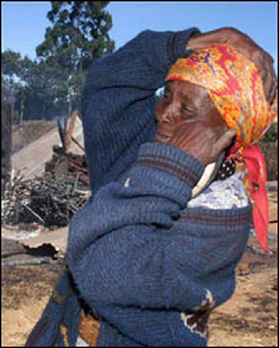 A woman reacts outside a Kenyan church that was torched by a mob.