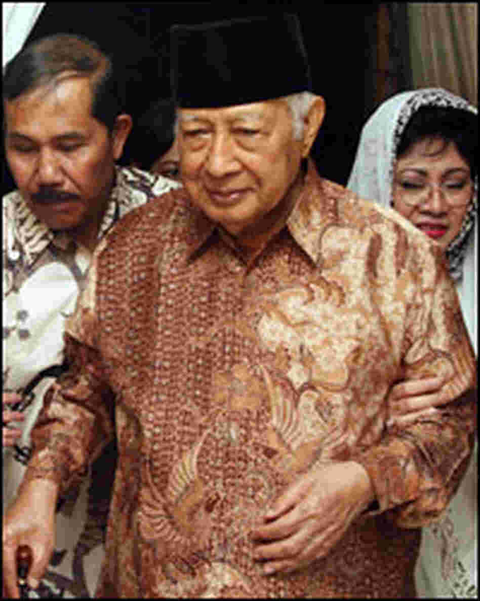 Former Indonesian President Suharto walks with his daughter Siti Hardiyanti Rukmana