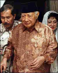 Former Indonesian President Suharto walks with his daughter Siti Hardiyanti Rukmana