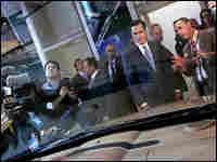 Mitt Romney looks over a Chrysler at the Michigan auto show.