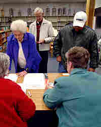 Voters line up to check with poll workers before voting during the South Carolina Democratic primary
