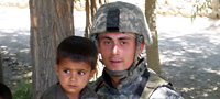 Cpl. Jason Bogar with a boy in Afghanistan.