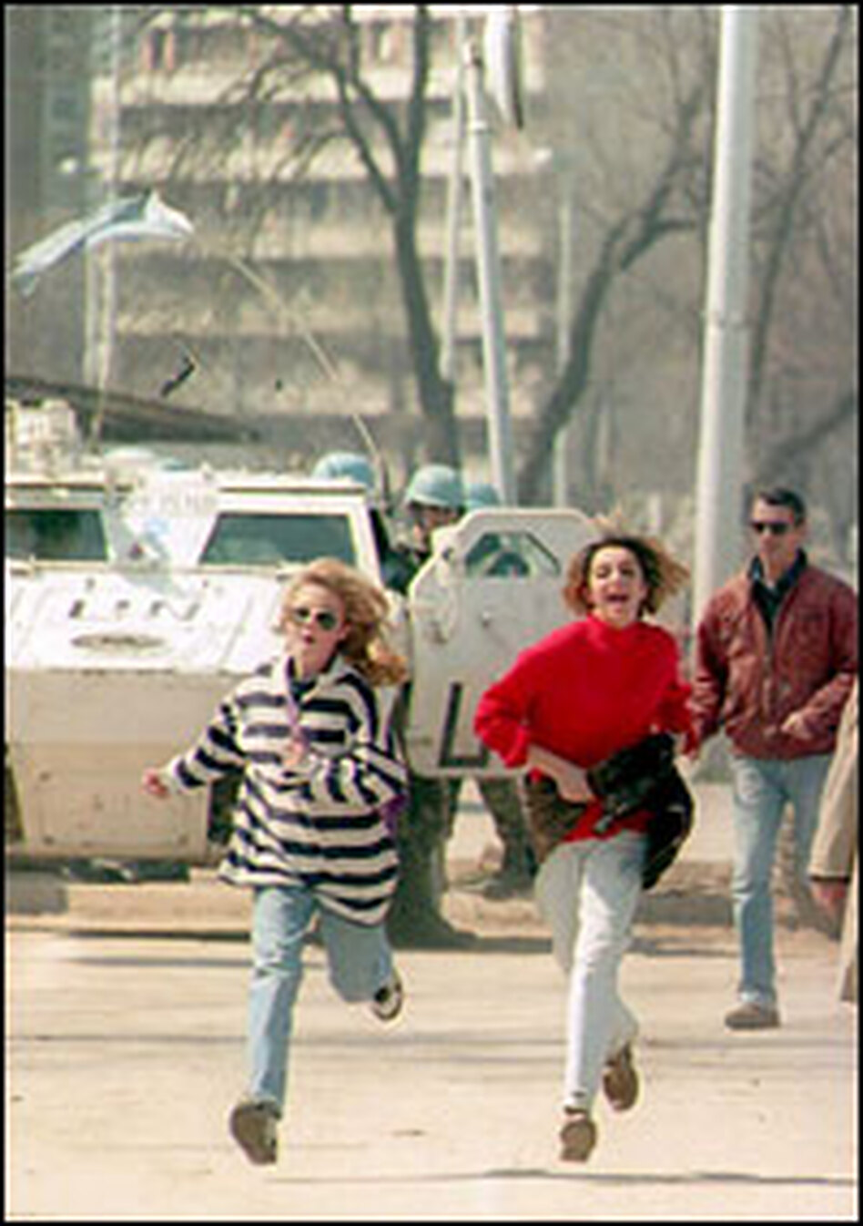 """Sarajevo residents run across the Bosnian capital's """"sniper alley"""" in April 1995, to avoid being shot at from Bosnian-Serb positions."""