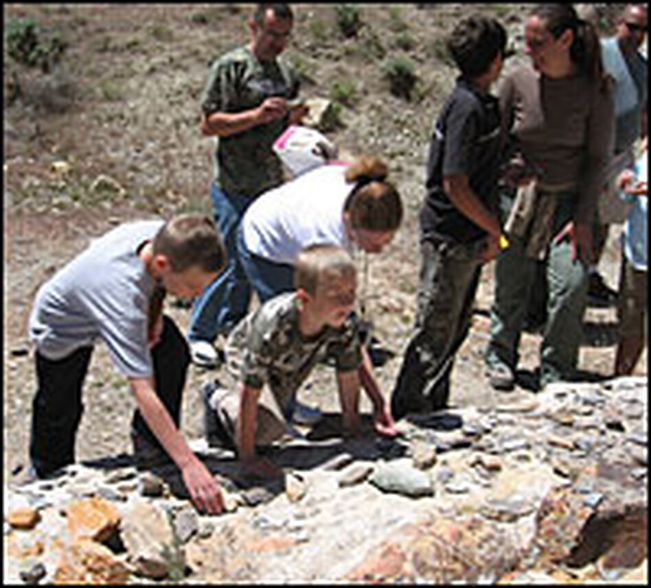 Aspiring junior paleontologist Justin Hazelwood (left) and his family look through shale for signs of fossilized fish scales.
