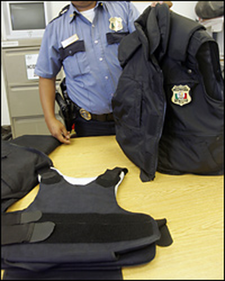A Juarez police officer displays his bulletproof vest, bought with his own money. On the table is the one issued to him by the Juarez police: a lightweight hand-me-down from the U.S. Border Patrol. The department's vest, he says, doesn't stop most bullets from the guns used by drug cartels.