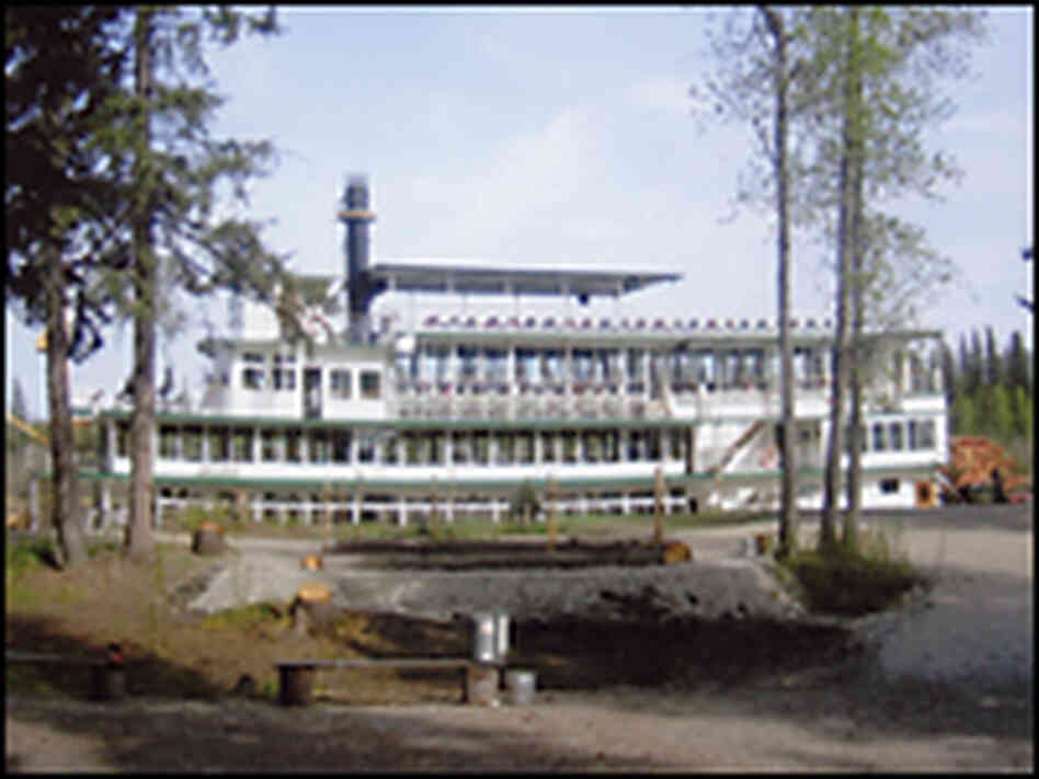 The Riverboat Discovery docked near a forest on the Chena River.