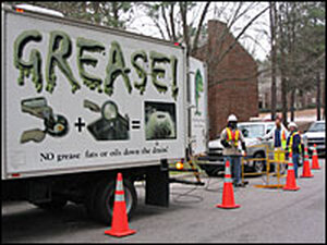 Raleigh public works employees use a specially equipped truck to clean grease out of a sewer line.