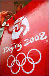 Workers install a billboard to mark the one-year milestone to the 2008 Olympic Games in Beijing.